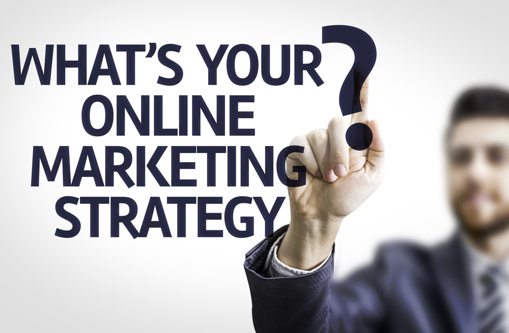 Business man pointing to transparent board with text Whats your Online Marketing Strategy?