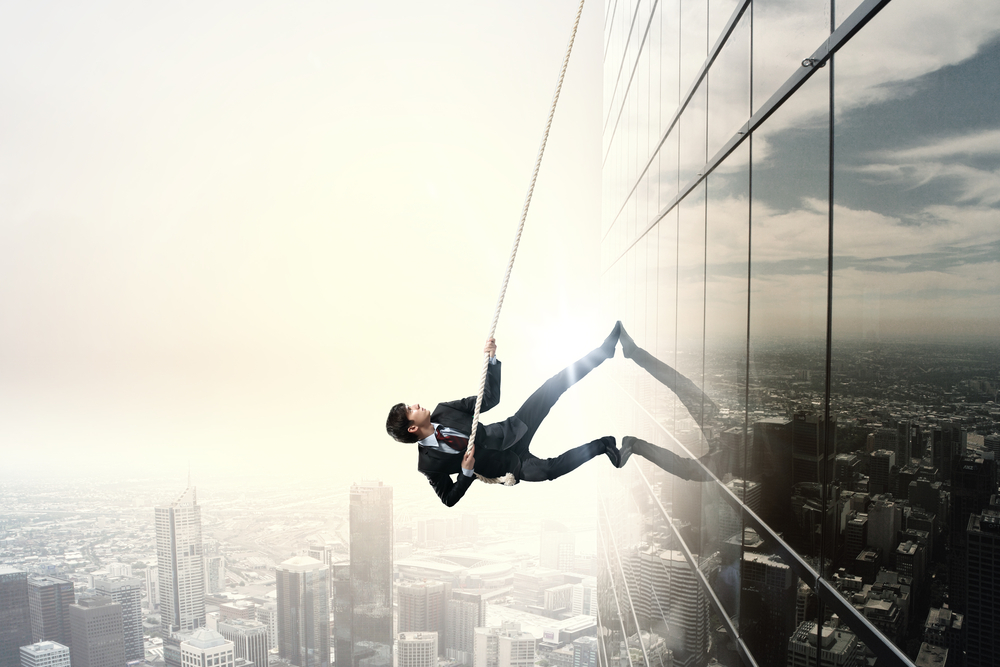 Determined businessman climbing building with help of rope