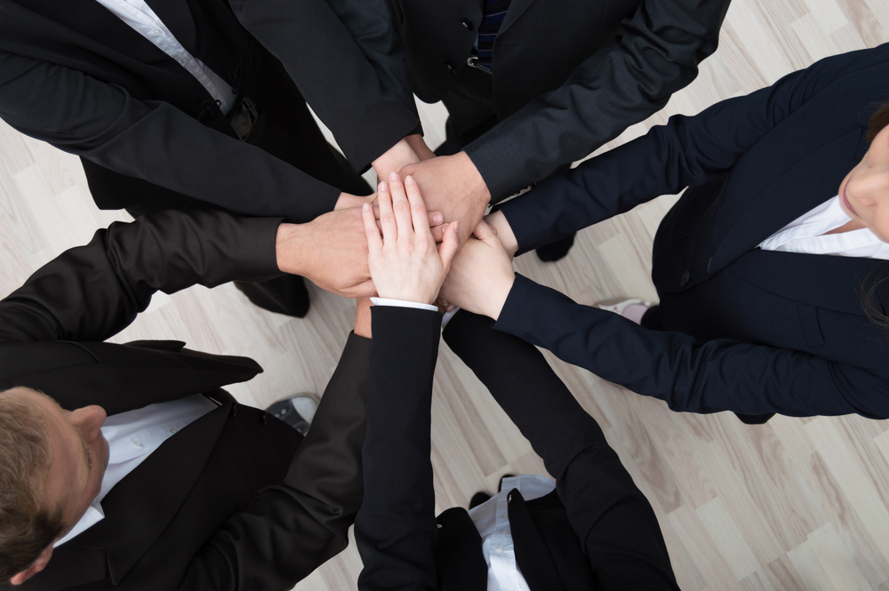 Teamwork - conceptual image of a group of young professional businesspeople standing in a circle facing each other clasping hands
